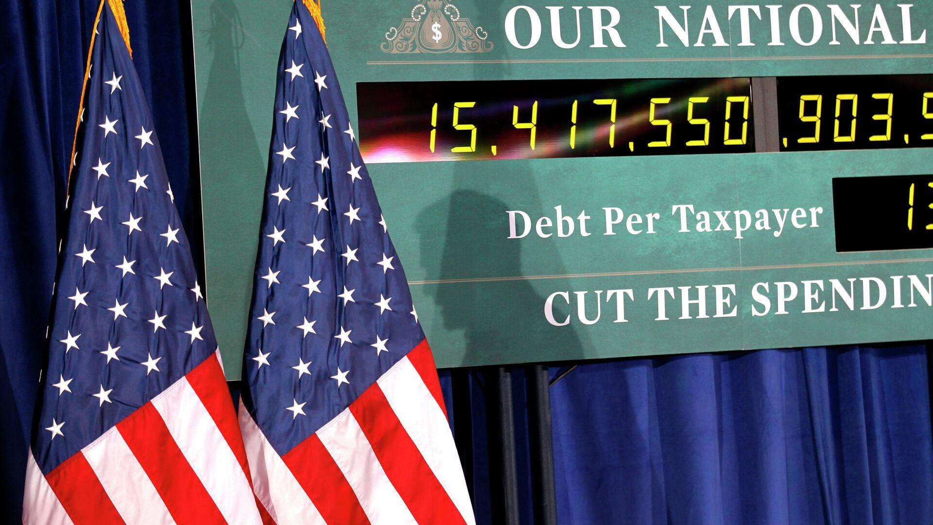 Тень кандидатав президенты США Митта Ромни на фоне часов, показывающих рост госдолга США - РИА Новости, 1920, 28.09.2021