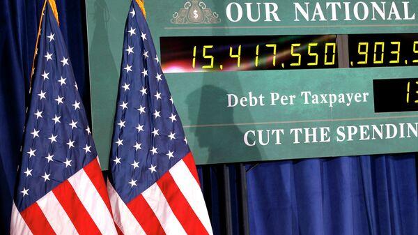 Тень кандидатав президенты США Митта Ромни на фоне часов, показывающих рост госдолга США