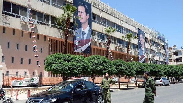 Плакаты с портретом президента Сирии Башаром Асадом на здании в Дамаске. Архивное фото