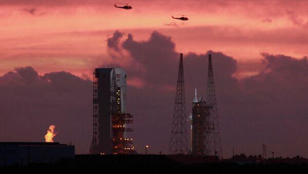 Военные вертолеты пролетают над стартовой площадкой космического корабля Orion
