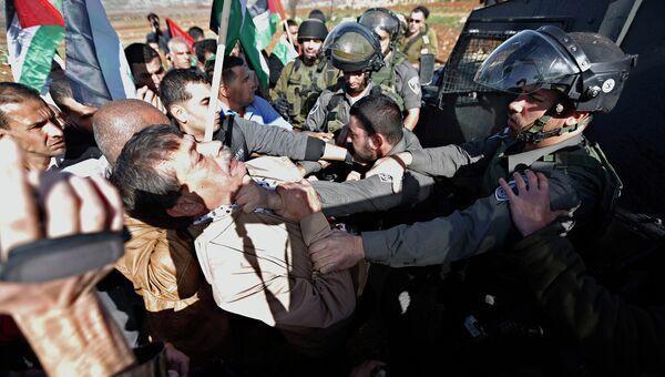 Министр палестинского правительства Зияд Абу Айн во время схватки с израильскими полицейскими. 10 декабря 2014. Архивное фото