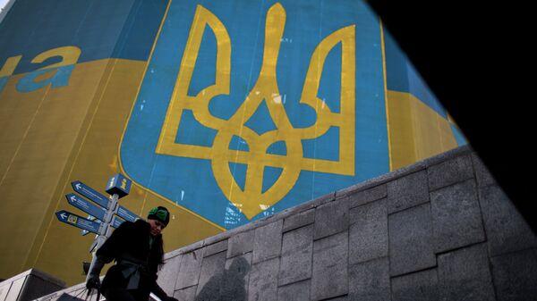 Женщина проходит мимо огромного украинского флага в центре Киева. Архивное фото