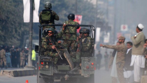 Пакистанские силы безопасности неподалеку от военного училища в Пакистане, захваченного боевиками. 16 декабря 2014