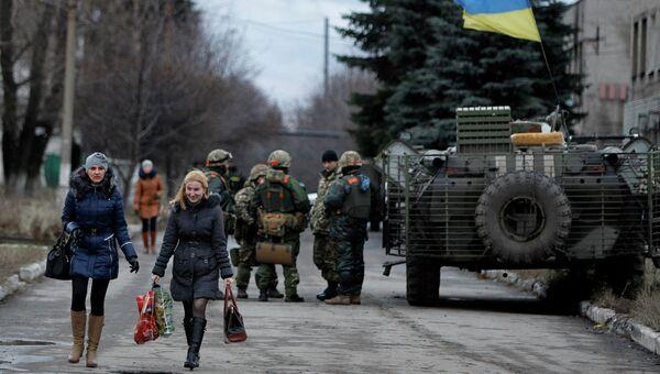 Местные жители проходят мимо солдат украинской армии в селе Дебальцево, Донецкая область. Архивное фото