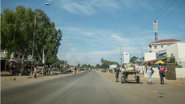 Люди проходят по улице в Банжуле, Гамбия