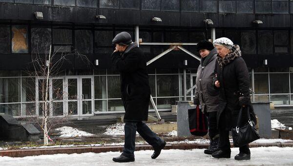 Жители Донецка на фоне поврежденного в результате обстрела здания. 1 февраля 2015