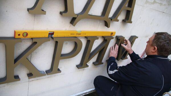 Рабочий крепит на фасад Государственного совета Республики Крым название парламента на украинском языке. Архивное фото