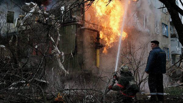 Пожарный тушит пожар в жилом доме, возникший в результате обстрела Донецка украинскими силовиками