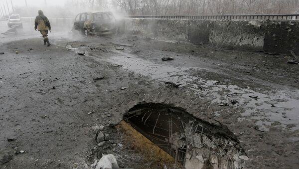 Место попадания снаряда и сгоревший автомобиль в Донецке после обстрела украинскими силовиками