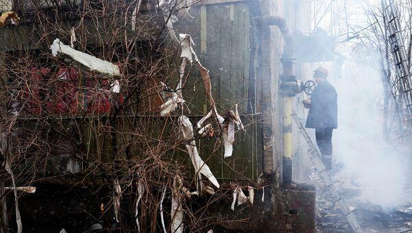 Работник коммунальной службы осматривает жилой дом, поврежденный в результате обстрела химического завода в Донецке