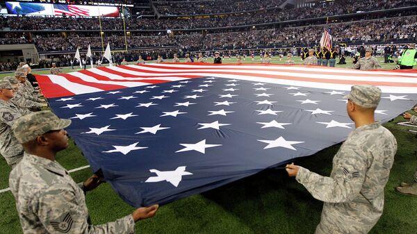 Военные США держат американский флаг на стадионе в Техасе. Архивное фото
