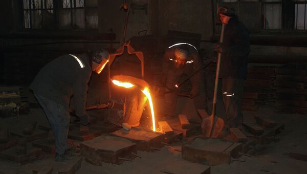 Рабочие во время плавки и разливки стали в формы на литейном участке. Архивное фото