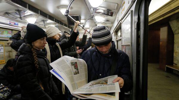 Молодой человек читает газету в Киевском метро. Архивное фото