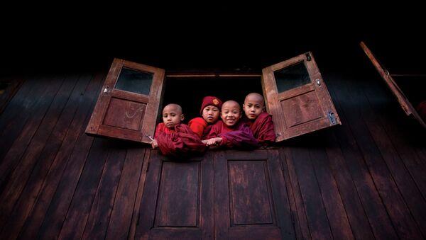Дети смотрят из окна буддийского монастыря