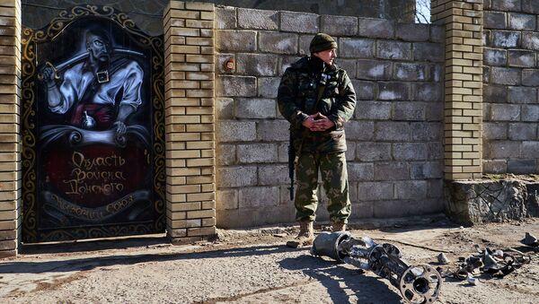 Ополченец возле обломков снаряда, выпущенного со стороны позиций ВСУ. Архивное фото
