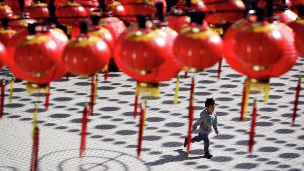 Мальчик бежит в храм под традиционными китайскими фонариками в Куала-Лумпуре