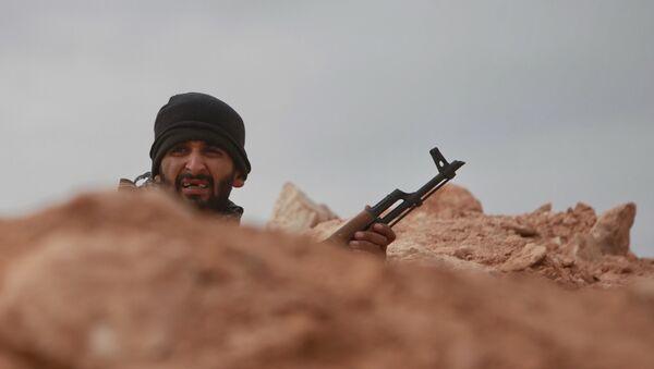 Боец прячется в укрытии во время боев за город Рас-Лануф. архивное фото