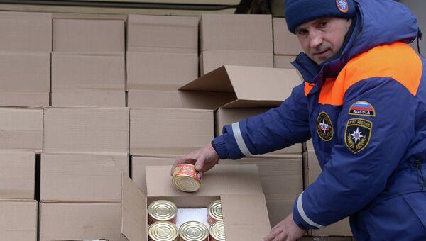 Сотрудник МЧС России демонстрирует банки с тушеной говядиной - гуманитарный груз одного из грузовых автомбилей шестнадцатого российского гуманитарного конвоя