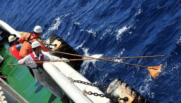Спасатели вылавливают из воды предметы на месте возможного крушения рейса MH370 авиакомпании Malaysia Airlines. Архивное фото