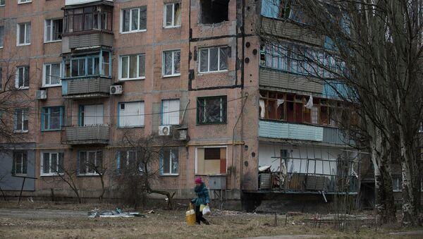 Женщина проходит мимо разрушенного жилого дома в Авдеевке, Украина, архивное фото