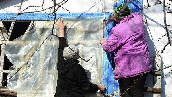 Жители села заклеивают разбитое окно. Архивное фото