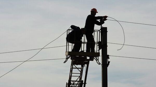Рабочие восстанавливают линию электропередач в Углегорске, Донецкая область. Архивное фото