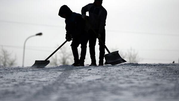 Сотрудники служб ЖКХ убирают снег
