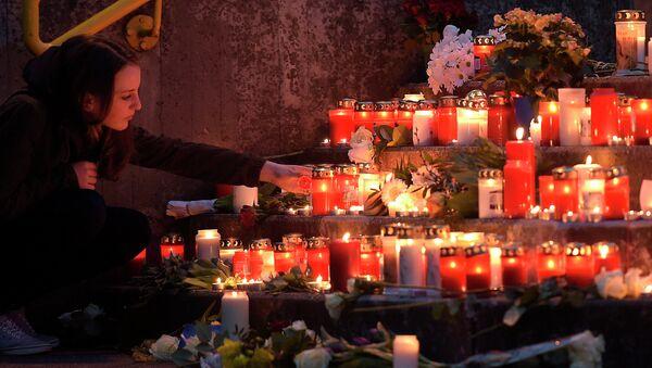 Девушка зажигает свечу в память о погибших пассажирах самолета Airbus A320 авиакомпании Germanwings. Архивное фото