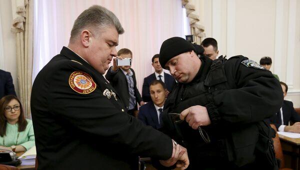 Полицейский надевает наручники на председателя Украинской государственной аварийно-спасательной службы Сергея Бочковского