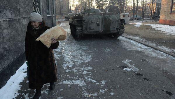 Пожилая женщина с хлебными лепешками после раздачи гуманитарной помощи жителям Дебальцево, которую привезли ополченцы