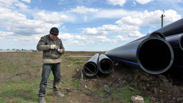 Рабочий выполняет работы по прокладке трубопровода от Северо-Крымского канала