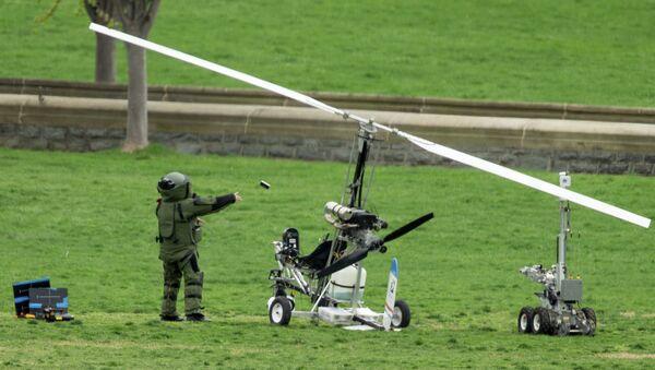 Сапер обследует вертолет, приземлившийся у здания конгресса США в Вашингтоне. 15 апреля 2015