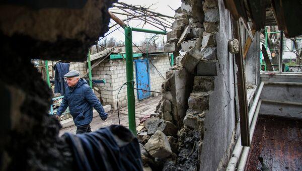 Мужчина рядом с разрушенным домом в селе Никишино Донецкой области