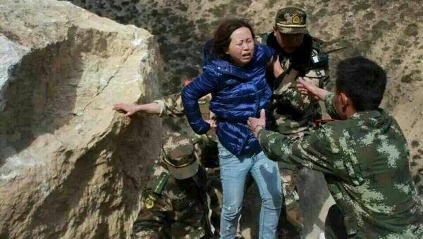 Спасатели помогают женщине в Тибетском автономном регионе Китая