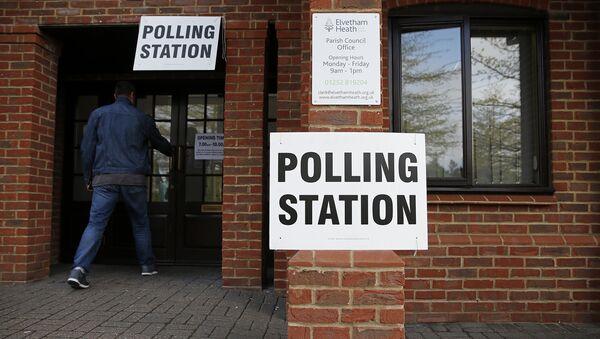 Мужчина заходит на избирательный участок во время парламентских выборов в Великобритании