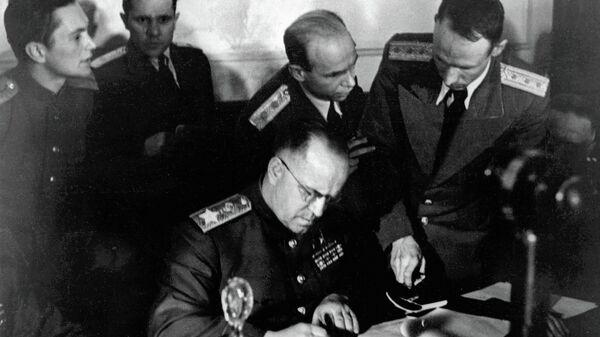 Маршал Советского Союза Георгий Константинович Жуков (в центре) подписывает Акт о безоговорочной капитуляции фашистской Германии в Карлсхорсте в Берлине