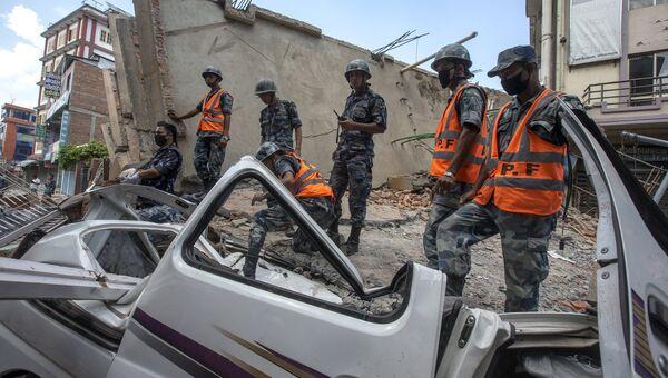 Военнослужащие стоят на разрушенном здании после новых толчков в Катманду. 12 мая 2015