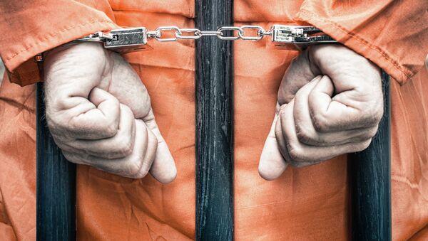 Заключенный в наручниках за решеткой. Архивное фото