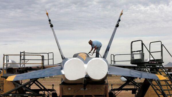 Военнослужащий покрывает водонепроницаемой краской американский истребитель-бомбардировщик F-18 на авиабазе ВВС США Девис-Монтен в Тусоне, Аризона. Архивное фото