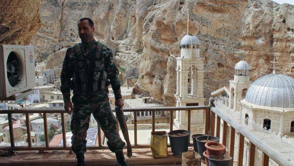 Военнослужащий сирийской армии на фоне церкви в городе Маалюля