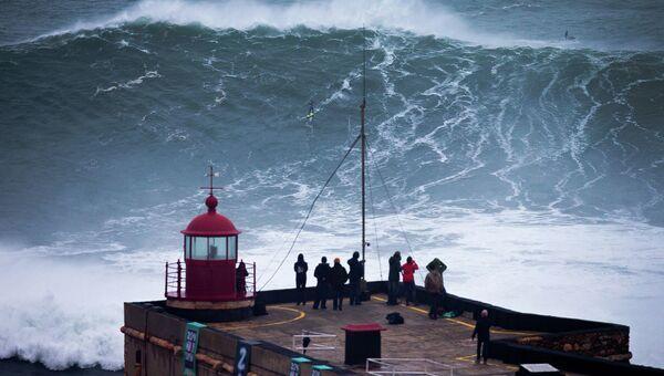 Люди наблюдает за тем, как серфер катается на волне возле рыбацкой деревни Назаре, Португалия