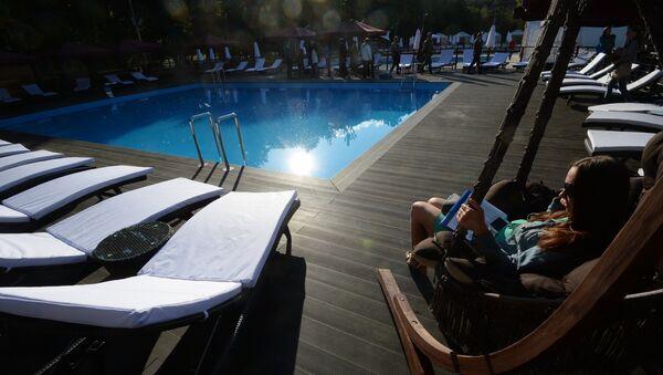 Девушка в кресле у бассейна на территории городского пляжа Порт на ВДНХ