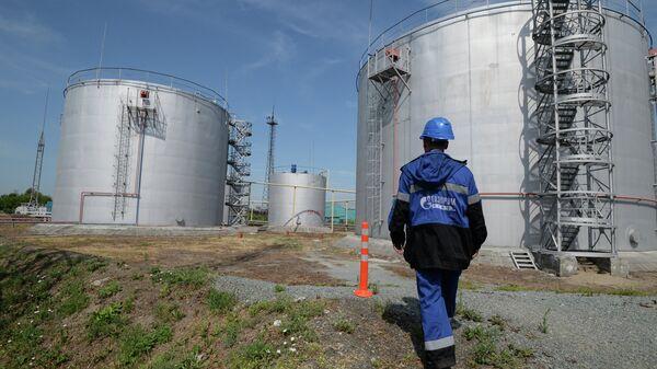 Сотрудник Новосибирской нефтебазы компании Газпром нефть возле резервуаров для хранения топлива. Архив