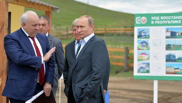 Президент России Владимир Путин (справа) и глава Республики Хакасия Виктор Зимин во время инспекции строительства домов для жителей села Усть-Бюр в Хакасии