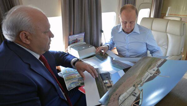 Президент России Владимир Путин (справа) и глава Республики Хакасия Виктор Зимин во время облета пострадавшей от пожаров территории Хакасии