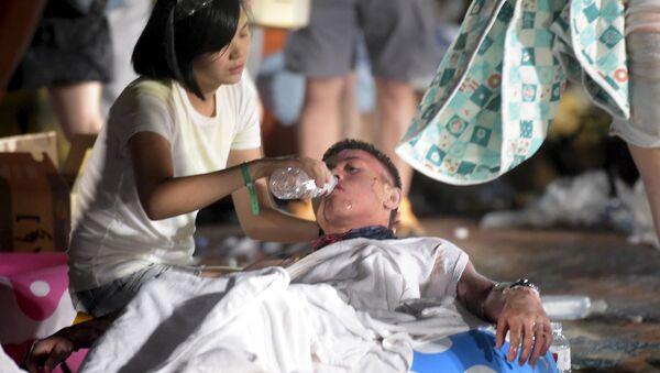 Волонтер оказывает помощь раненому при ЧП в парке развлечений в Тайване