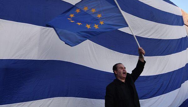 Мужчина держит флаг Евросоюза во время проевропейской демонстрации в Афинах
