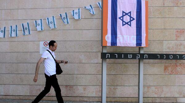 Мужчина у входа в офис сотового оператора Партнер тикшорет, работающей под брендом французской компании Оранж в городе Рош ха-Аин, Израиль