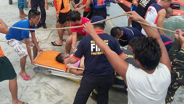 Спасатели несут пассажира затонувшего парома в Маниле, Филиппины