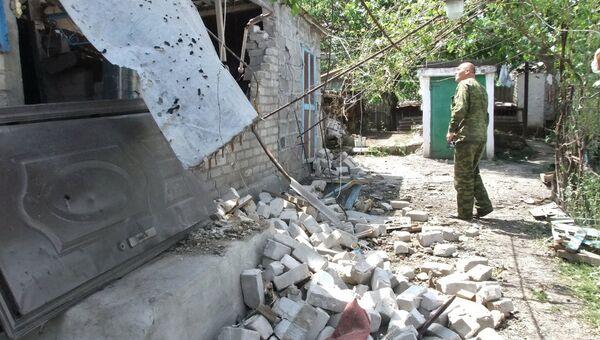 Мужчина у дома, поврежденного в результате обстрела украинскими силовиками, в селе Саханка Донецкой области. 2 июля 2015